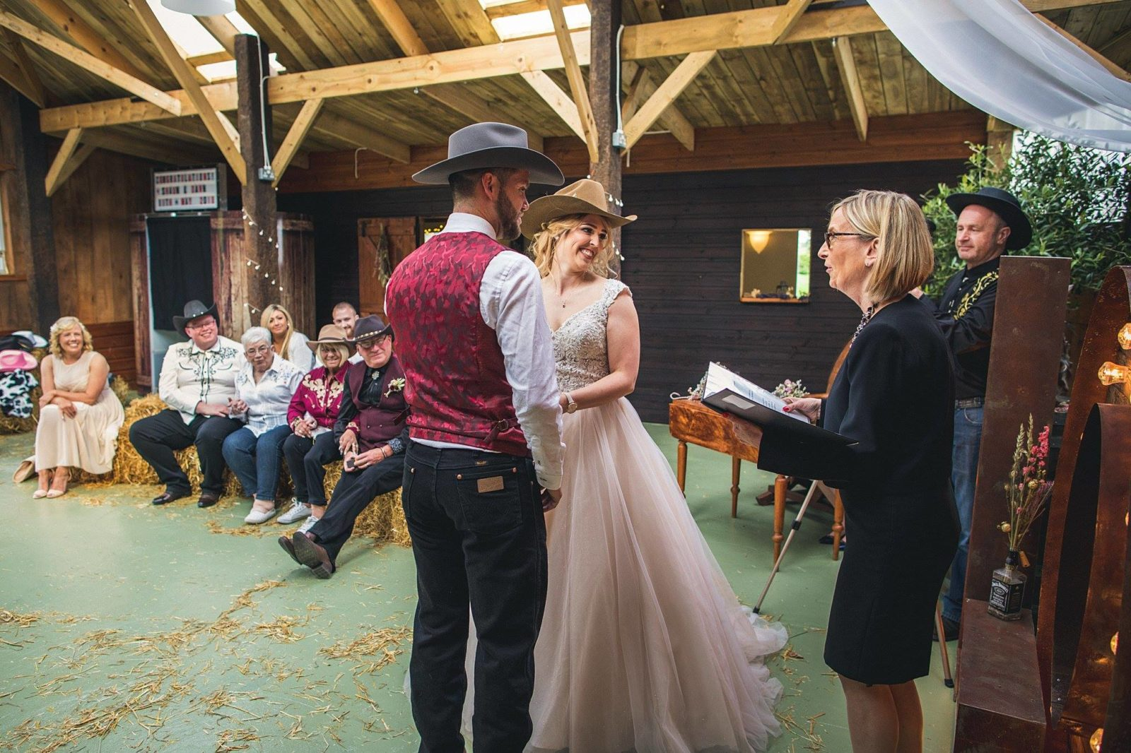 bride and groom wearing cowboy hats in barn wedding
