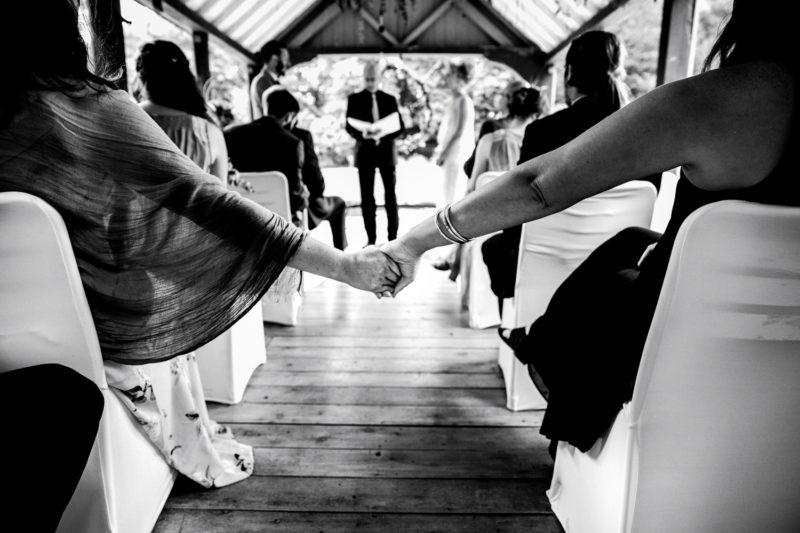 Guests holding hands at boathouse wedding ceremony