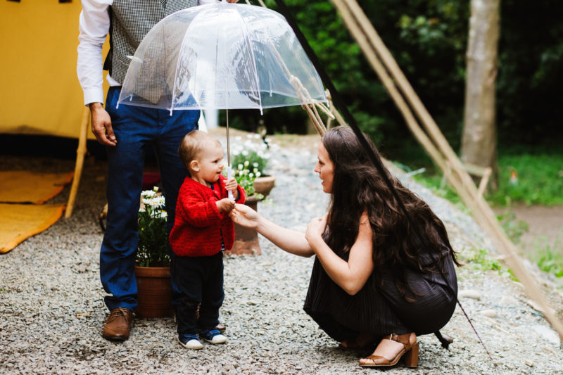 Toddler holding umbrella with wedding guest