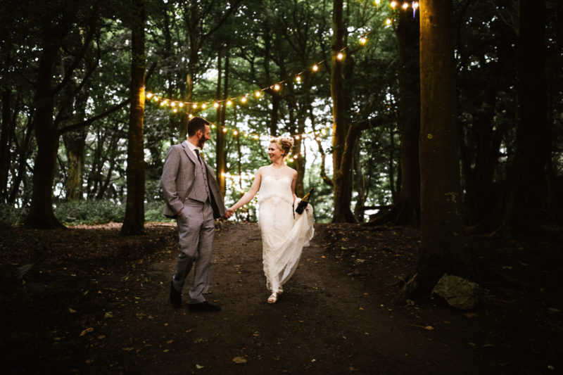 Alternative bride and groom walking through forest with festoon lighting