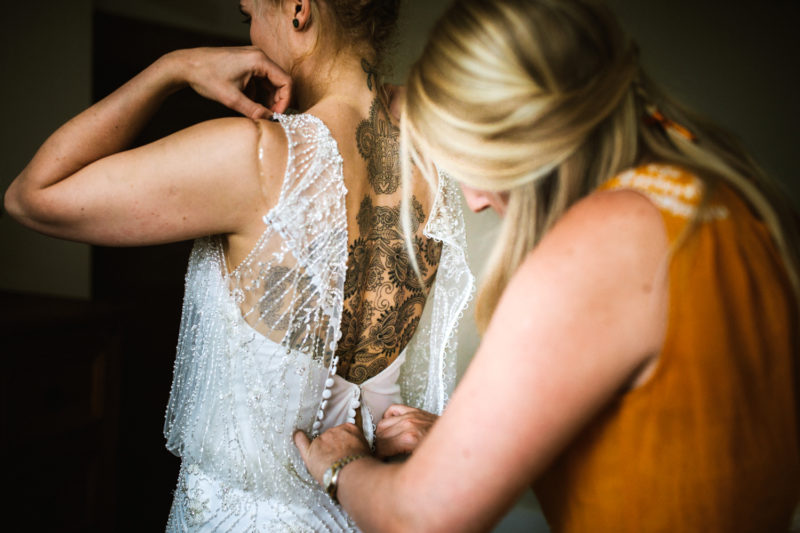 Tattooed bride being buttoned into her Justin Alexander wedding dress