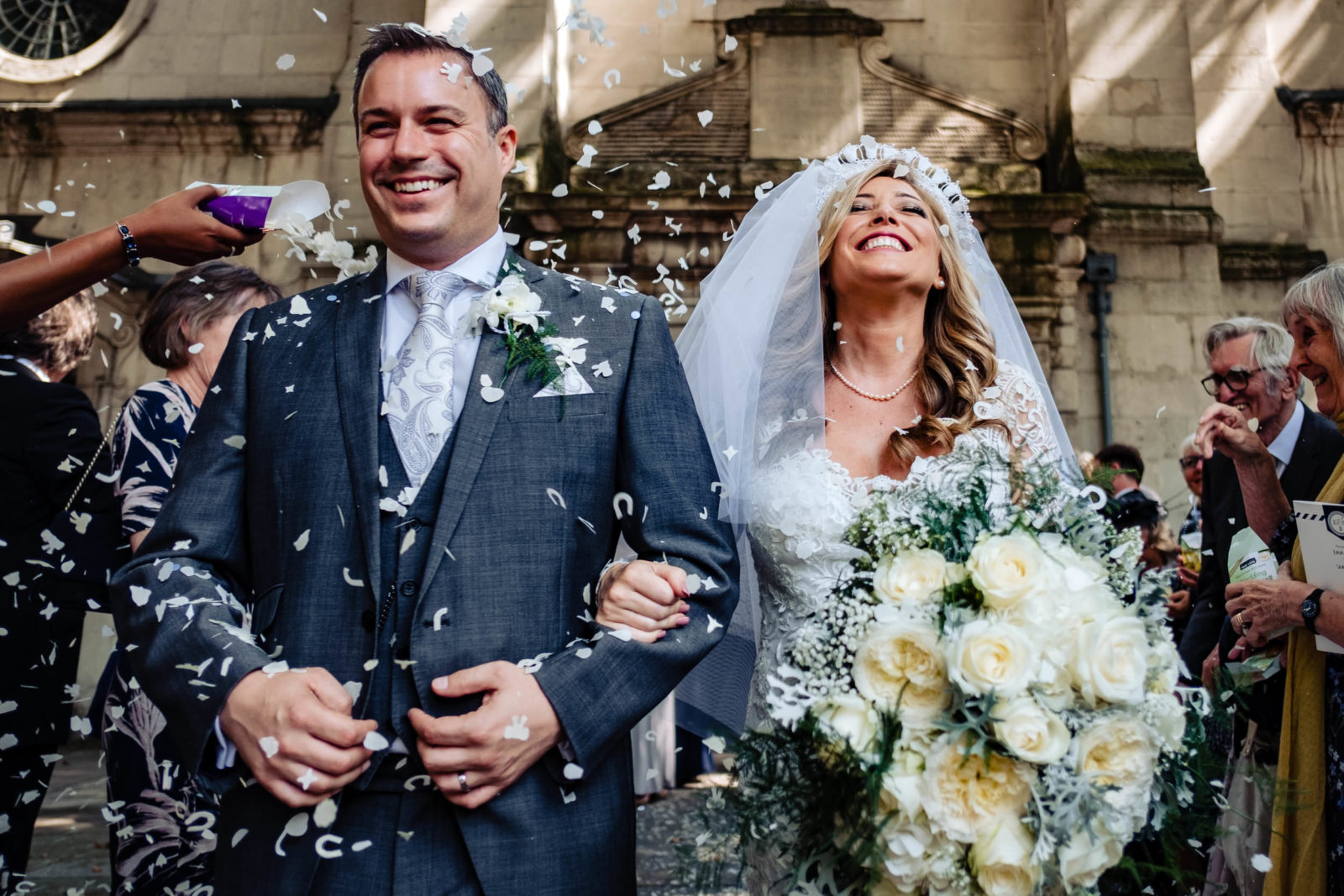 Bride and groom smiling covered in confetti