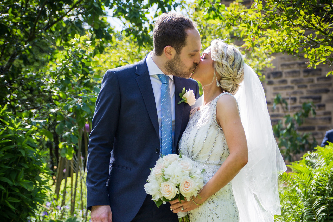 Bride with beaded gown and pale pink roses kissing groom