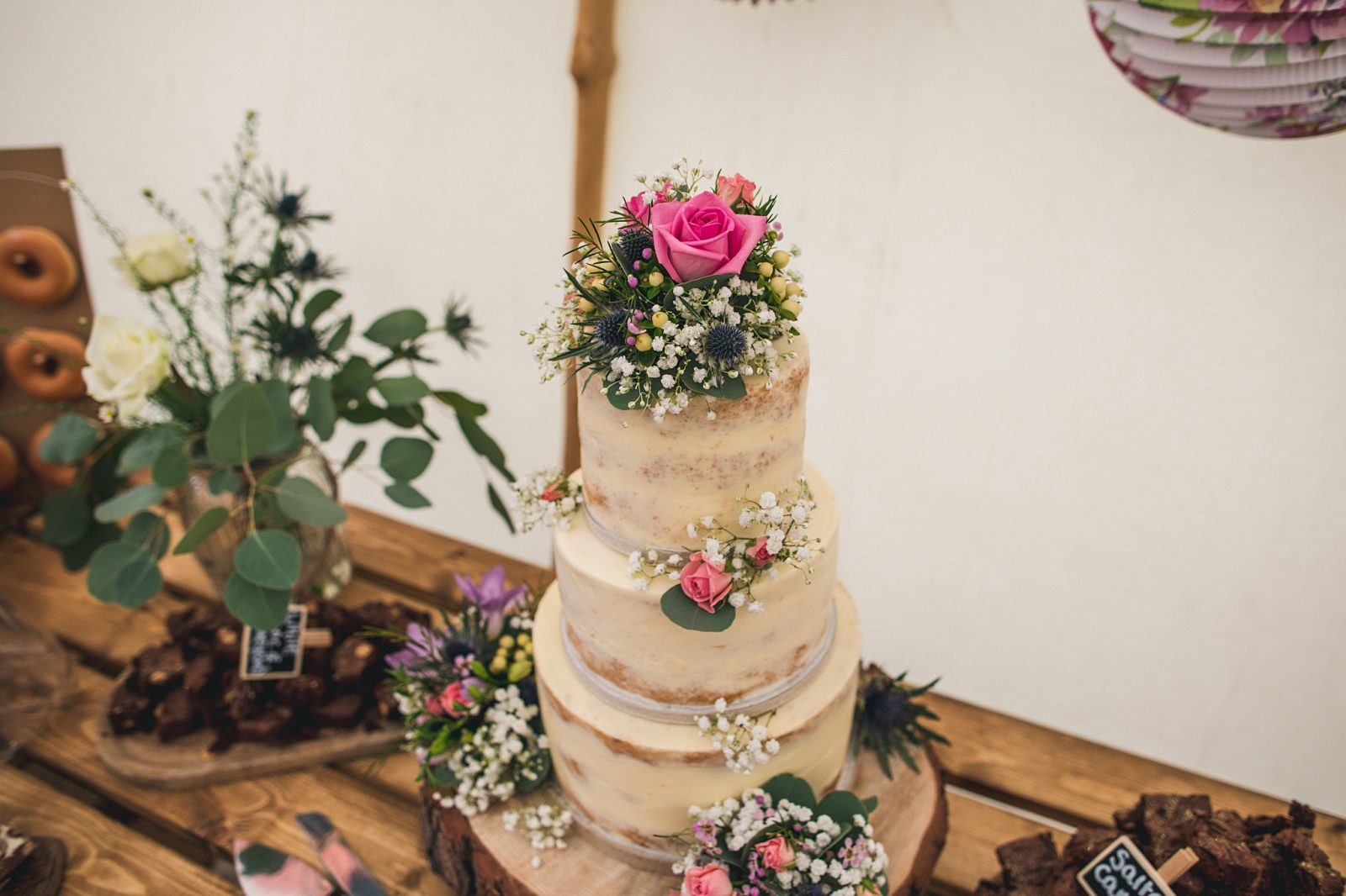 Semi naked wedding cake Ivory Cake Company decorated with flowers Andy Hudson Photography