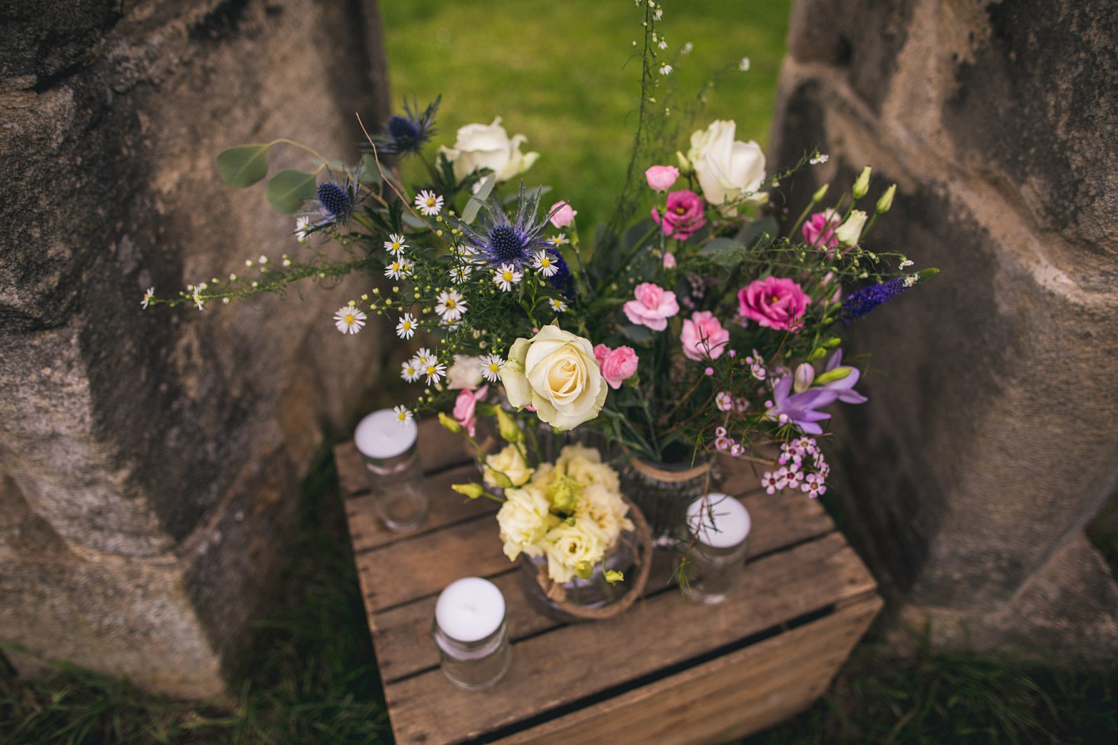 wedding reception ideas Roses thistles fresias gypsophila jam jars candles crate outdoor wedding