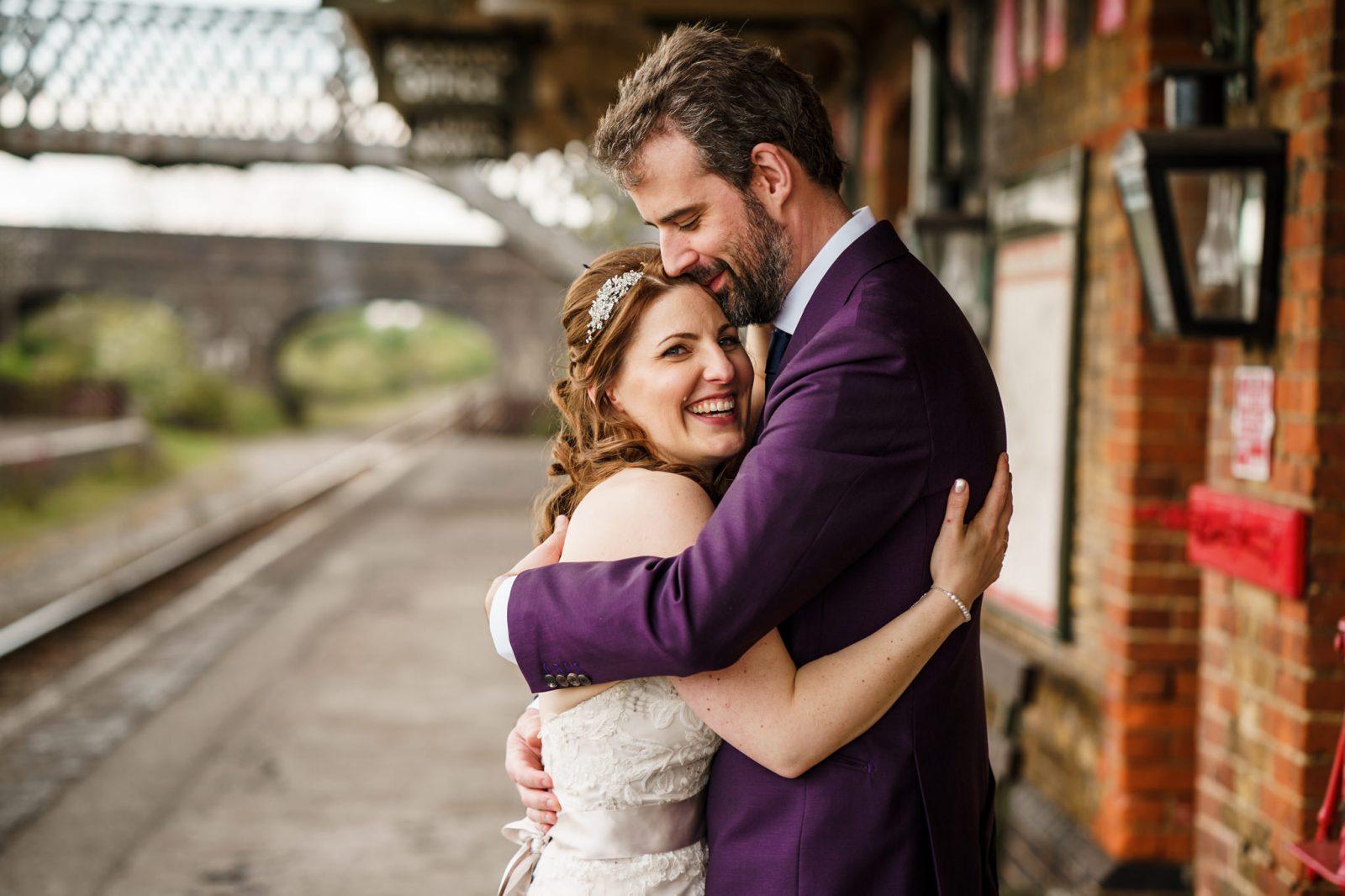 Purple-suit-groom-hugging-bride-train-station