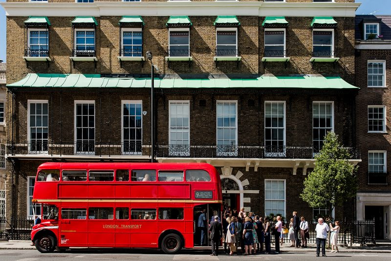 red double decker bus outside London pub real wedding