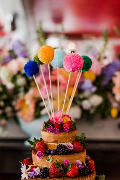 Naked wedding cake pompoms flowers fruit