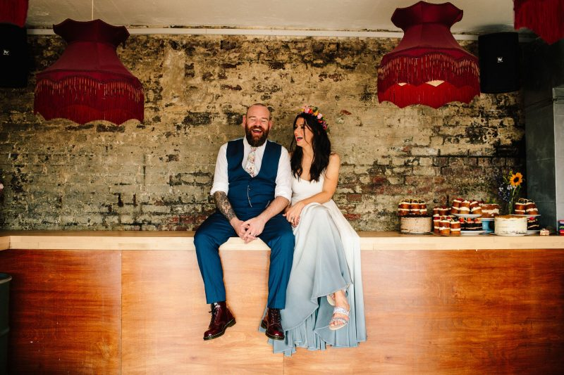 Bride groom laughing blue dipped hem wedding dress