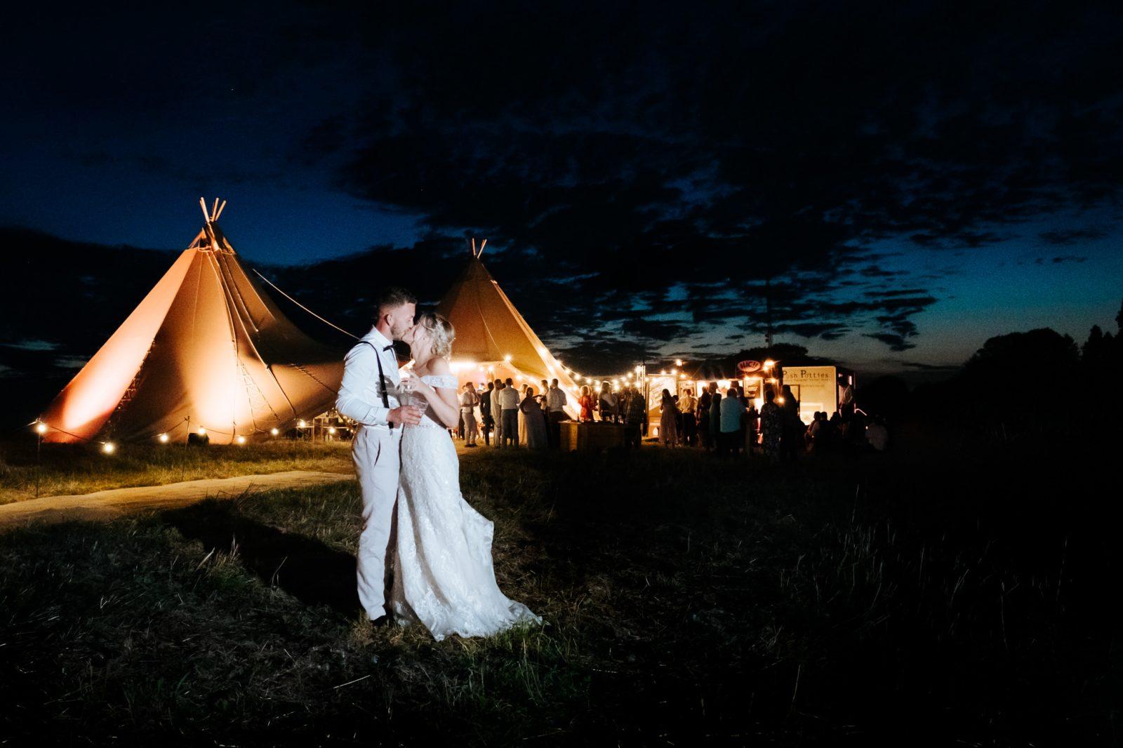 bride groom outside wedding tipi lit up